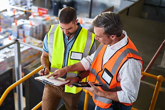 Two workers reviewing information on a clipboard in a warehouse